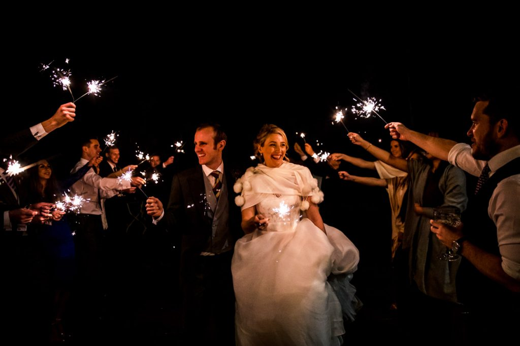 bride and groom with sparklers at night