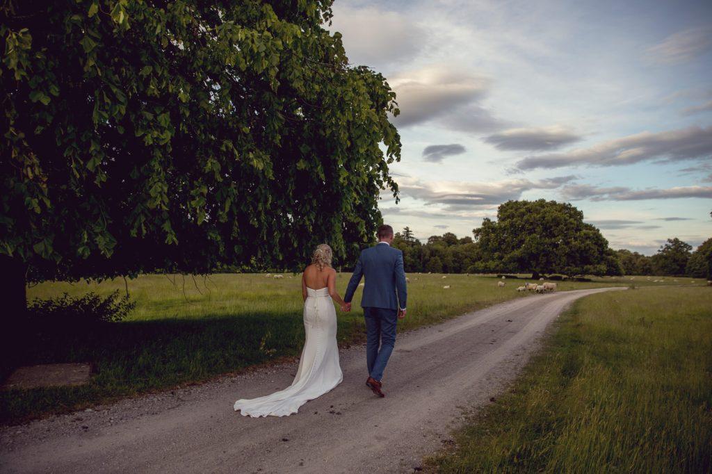 Lartington hall wedding bride and groom walking at sunset along the lane