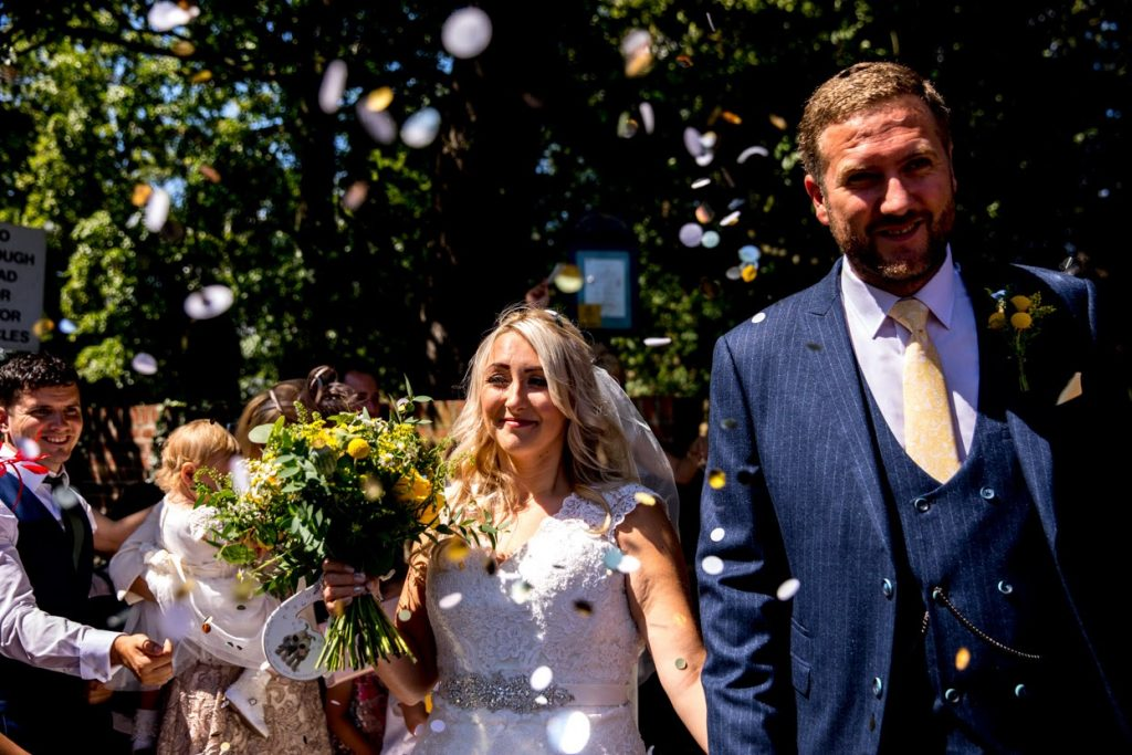bride and groom at walworth castle wedding having a confetti line